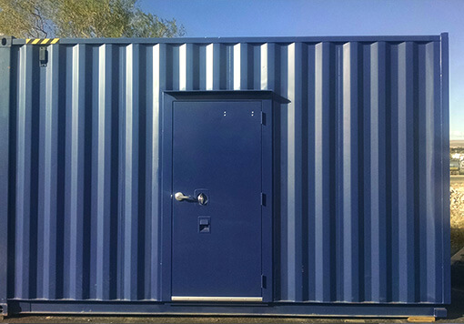 a blue storage container with a blue door, behind the container is a tree and the blue sky.