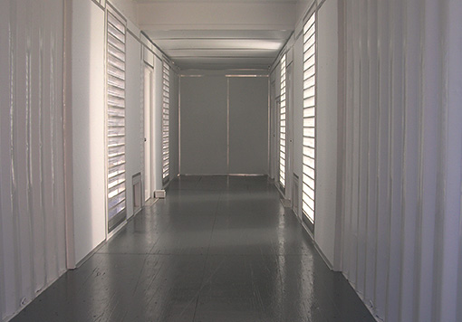a white storage container with some ventilation on it, it also has a gray door and a gray floor.