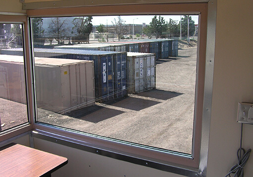 a window inside a storage container, outside the storage container are nine more containers in different colors, there are also some trees outside.