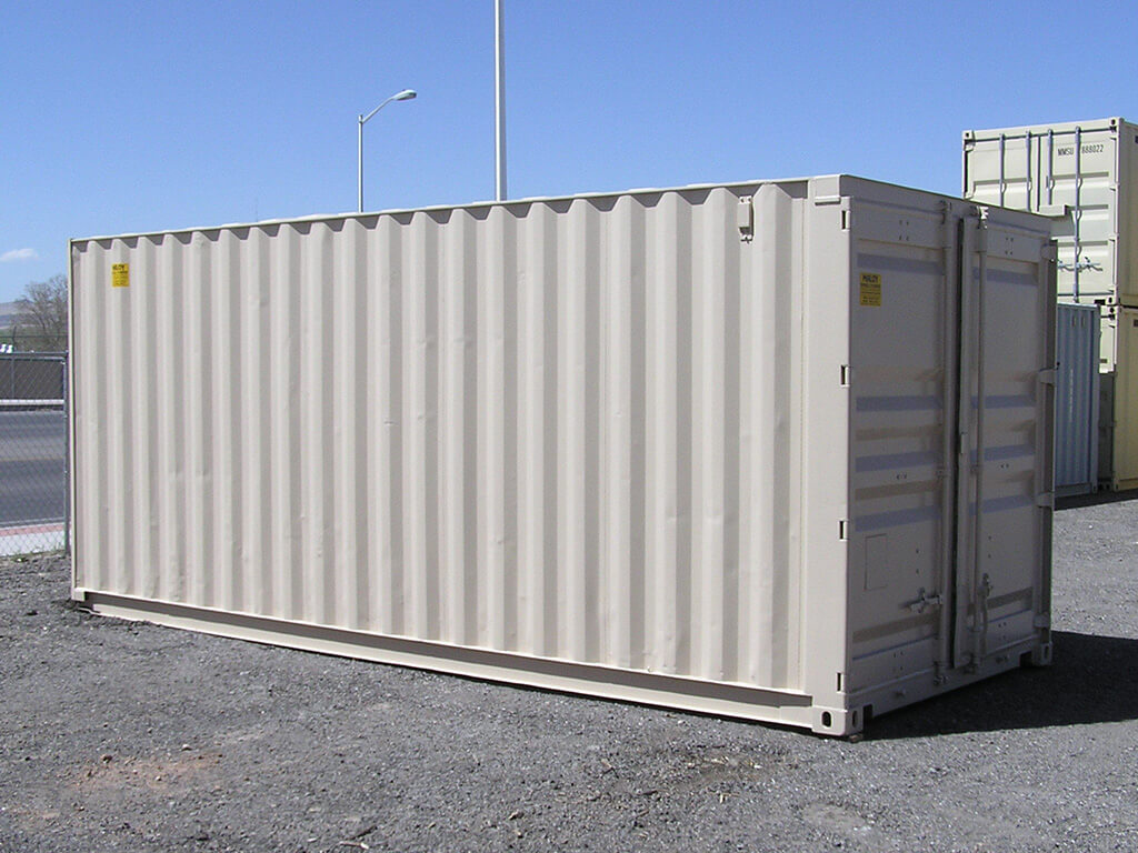 A 20ft storage container with a dirty white painted on it, behind the container are more storage containers and a road.