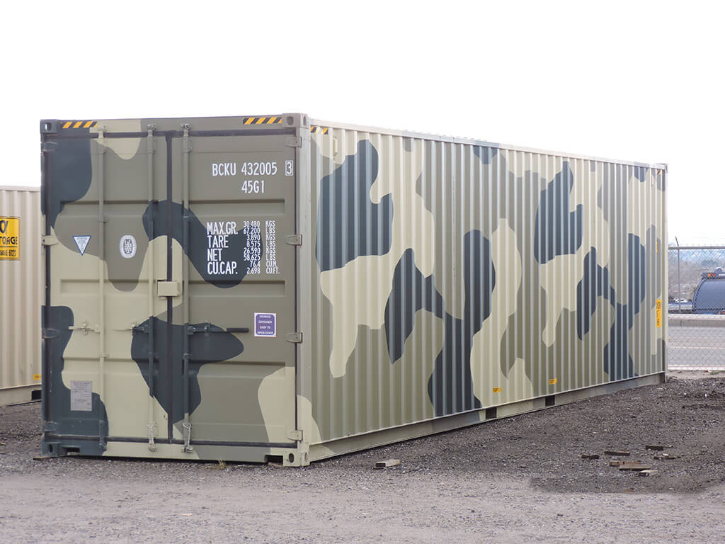 a storage container that was painted in Camouflage, it is a 40ft storage container, beside it is another storage container colored in dirty white.