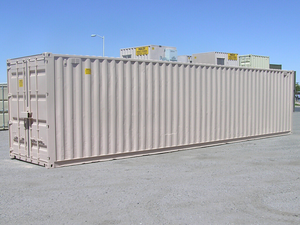 a 45 ft dirty white container with a yellow sticker in it saying maloy mobile storage with the company contact number, behind the container are more storage containers with different colors.