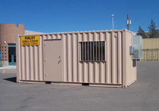 A flesh colored mobile storage with a door, window, electrical boxes, and with the company logo of Maloy Mobile Storage that is one of the storage containers Albuquerque and with a concrete building and blue sky as a background.
