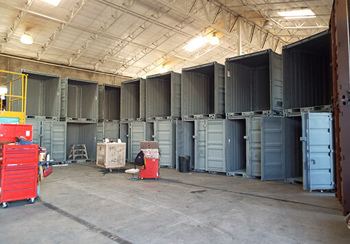 Goup of piled-up shipping containers with all of the doors open and which are placed inside a large factory that produces Albuquerque storage containers.