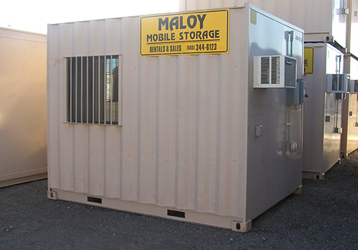 Small, rectangular, and flesh colored storage container that is modified as an office with window and air conditioner with the logo of Maloy Mobile Storage and along with the other mobile storages which are the products of Albuquerque storage containers.