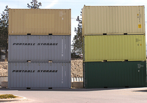 2 columns which consists of 3 piled portable storages with different colors and with trees as their background and which is one of the products of Albuquerque storage containers.