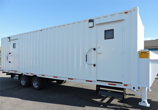 White rectangular and customized portable mobile storage with 2 doors, wheels, and that is one of the products of Albuquerque storage containers and with a blue sky as a background.