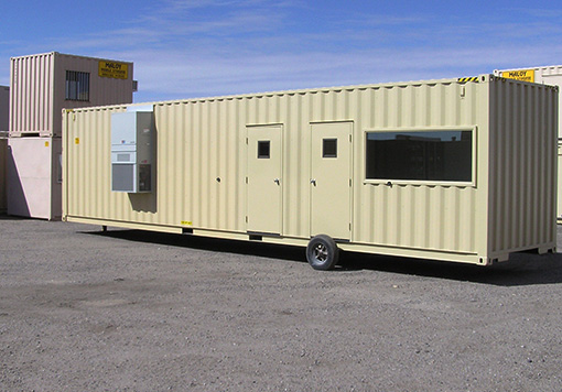 Portable mobile storage with the company logo of Maloy Mobile Storage with 2 doors, air conditioner, and glass windows is parked in front of the other piled up mobile storages and which is one of the products of Albuquerque storage containers.