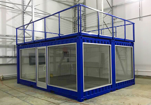 Storage container in a form of a modular office with a door and window glass with a mini balcony on its top and colored in a blue paint and that is placed on a factory of storage containers Albuquerque.