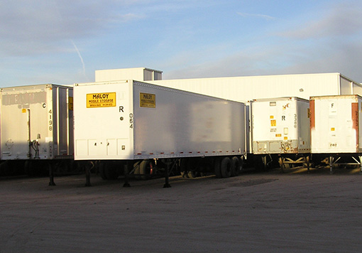 Portable mobile storage containers Albuquerque with the company logo of Maloy Mobile Storage are parked at the back of a white building with the sky and sunlight as a background.