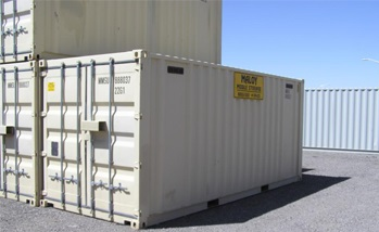 three white storage container piled up on each other, one container has a yellow sign which says Maloy Mobile Storage, behind the containers are a light blue container.