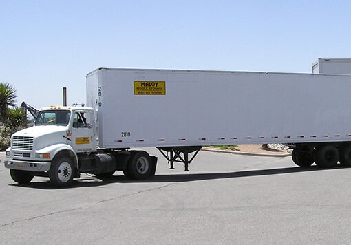 Long and white colored truck trailer with the company logo of Maloy Mobile Storage is on the middle of a concrete road and that is one of the products of Albuquerque storage containers.